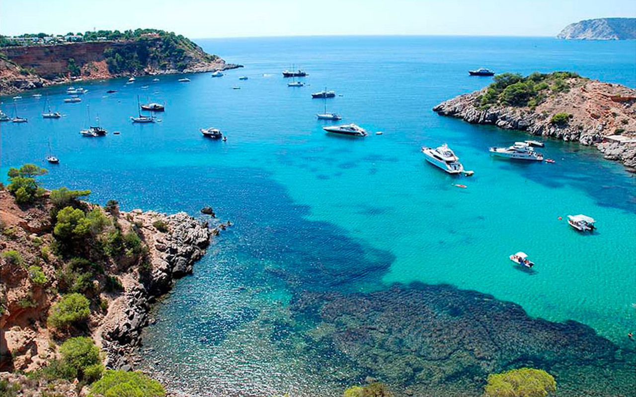 Charter boats rest in the turquoise waters of Cala Porroig (Ibiza).
