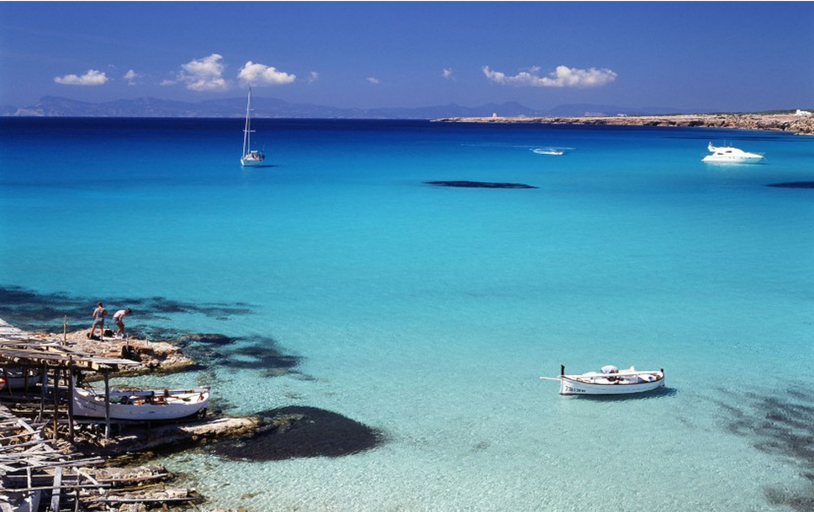 Rental boats anchored in the turquoise waters of Cala Saona (Formentera).