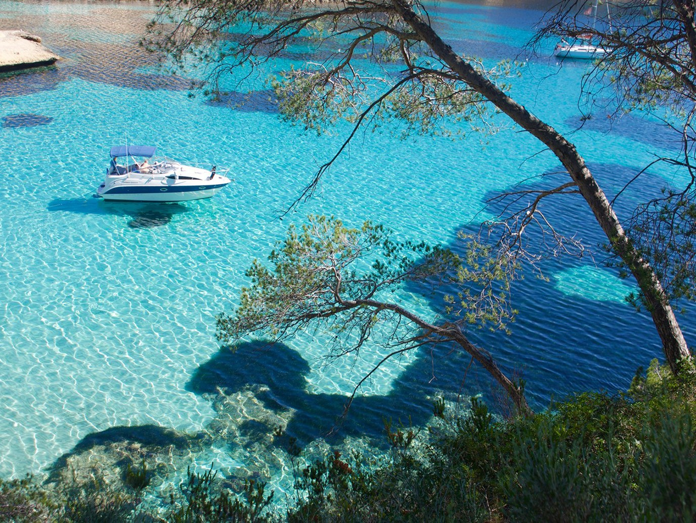 Motorboat anchored in the crystal clear waters of the mediterranean cala del Mago (Majorca)