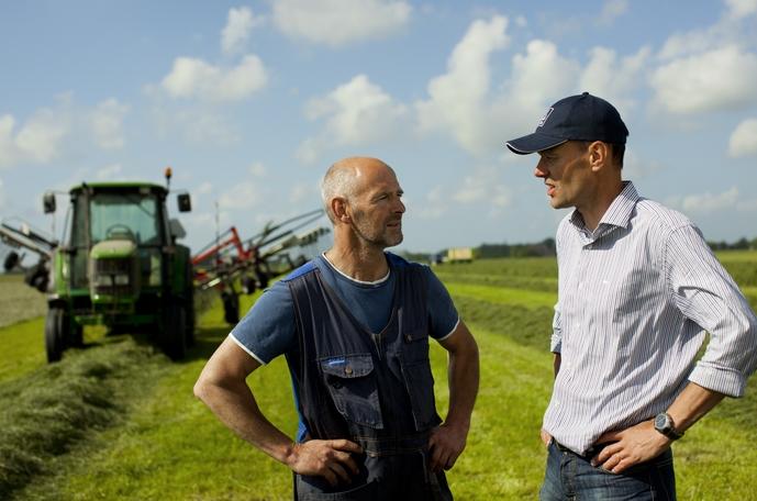 Två män som samtalar vid en traktor