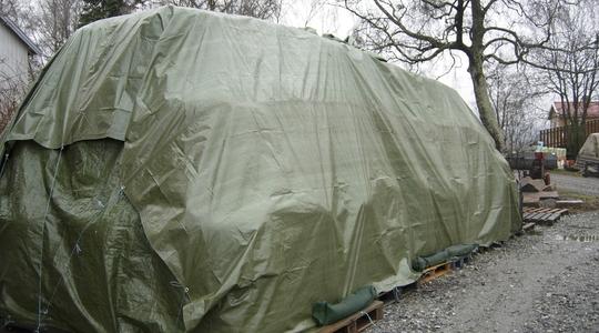 Pallförvaring utomhus täckt med presenning.