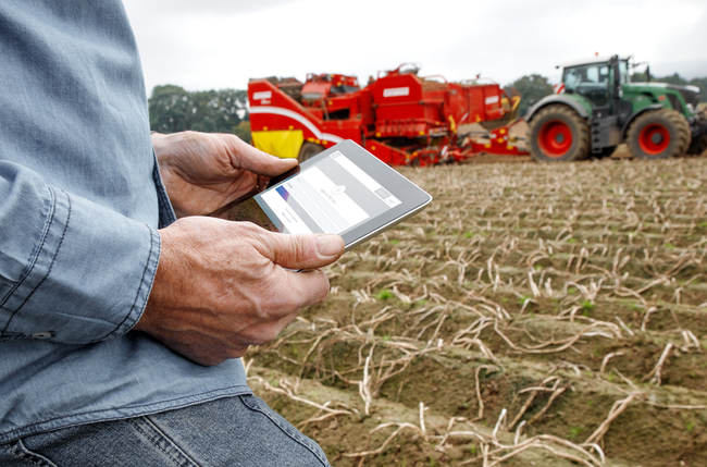 Farmer in a ploughed field holding an iPad