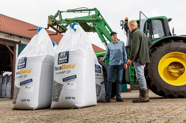 Farmer and agronomist with big bags of fertilizer