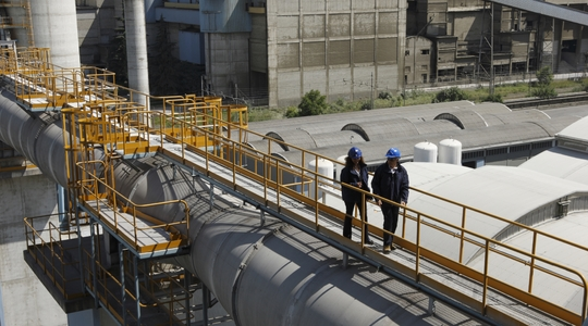 2 people walking at cement plant, pipes, height