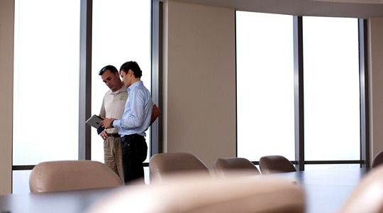 Two men in meeting room with big windows