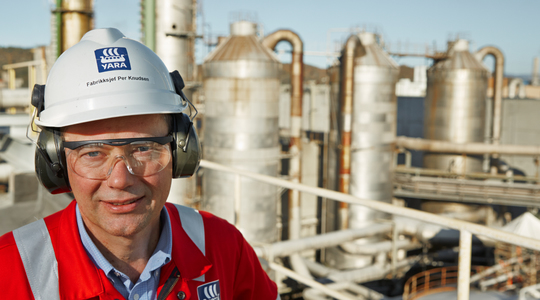 Man in front of nitric acid plant