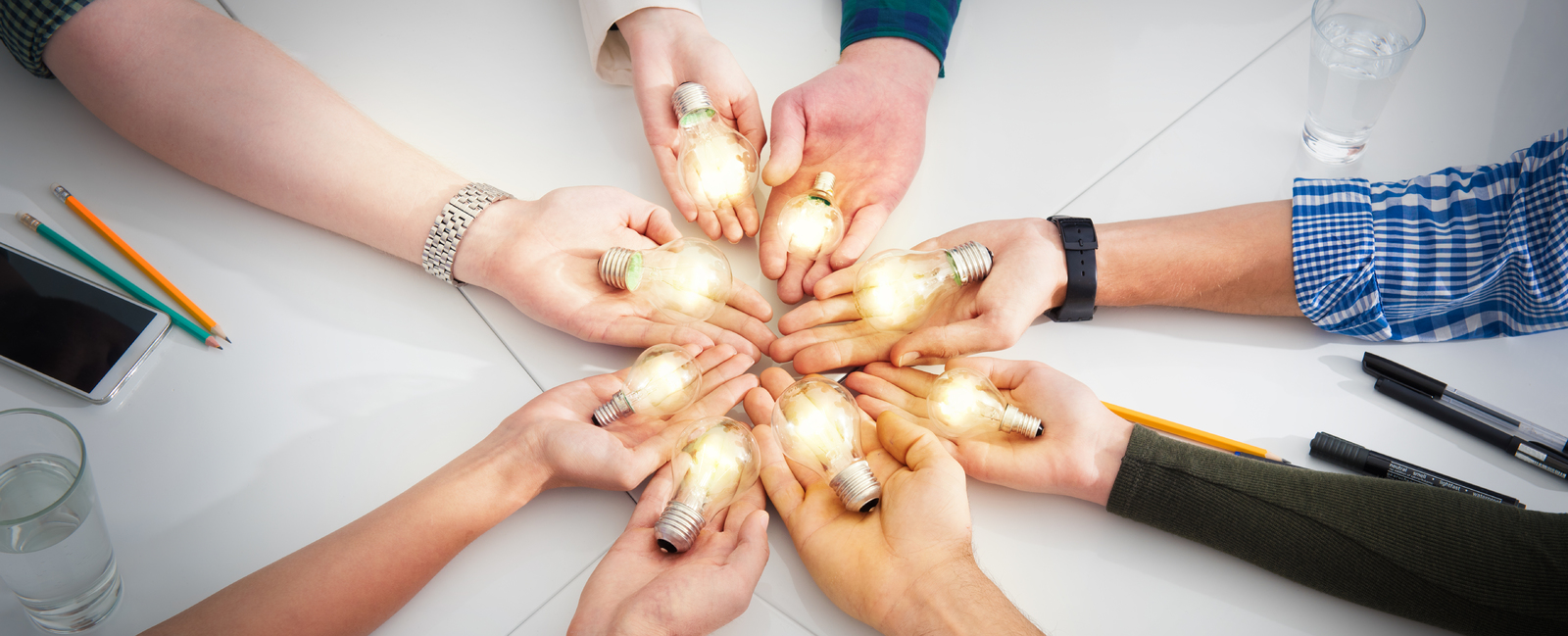 Group of hands holding light bulbs