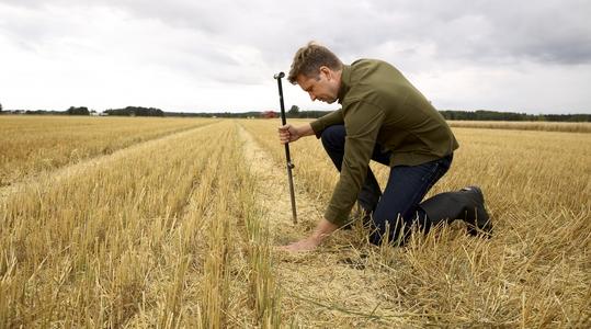 En man som markkarterar ett fält