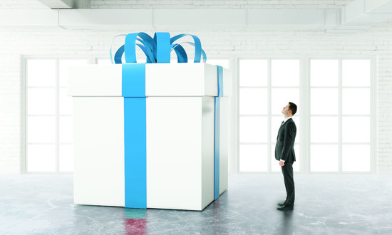 Man looking at an enormous gift with a blue bow