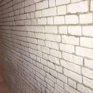 Parement type briques posé chez des clients sur un mur de salon Victor